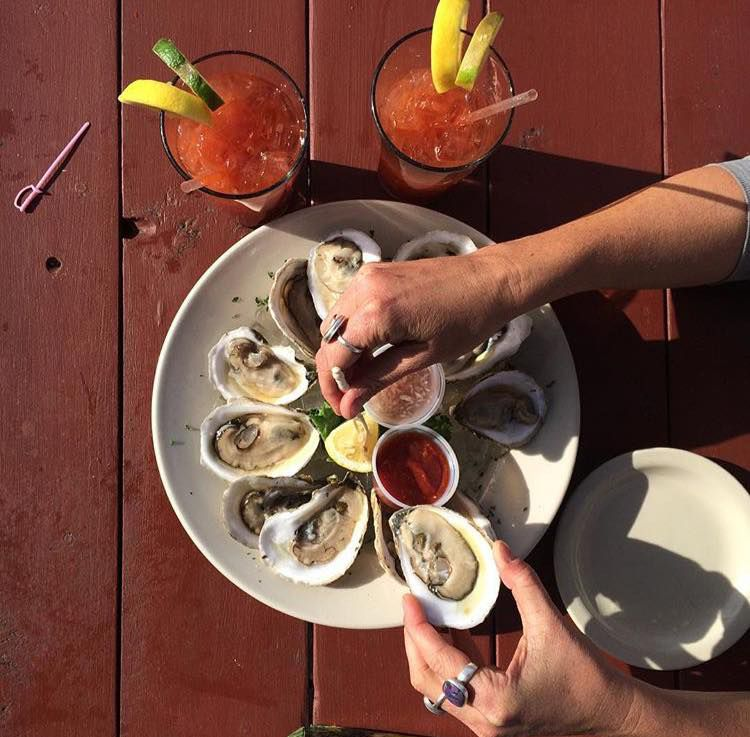 overhead shot of oysters on the half shell with two hands preparing an oyster