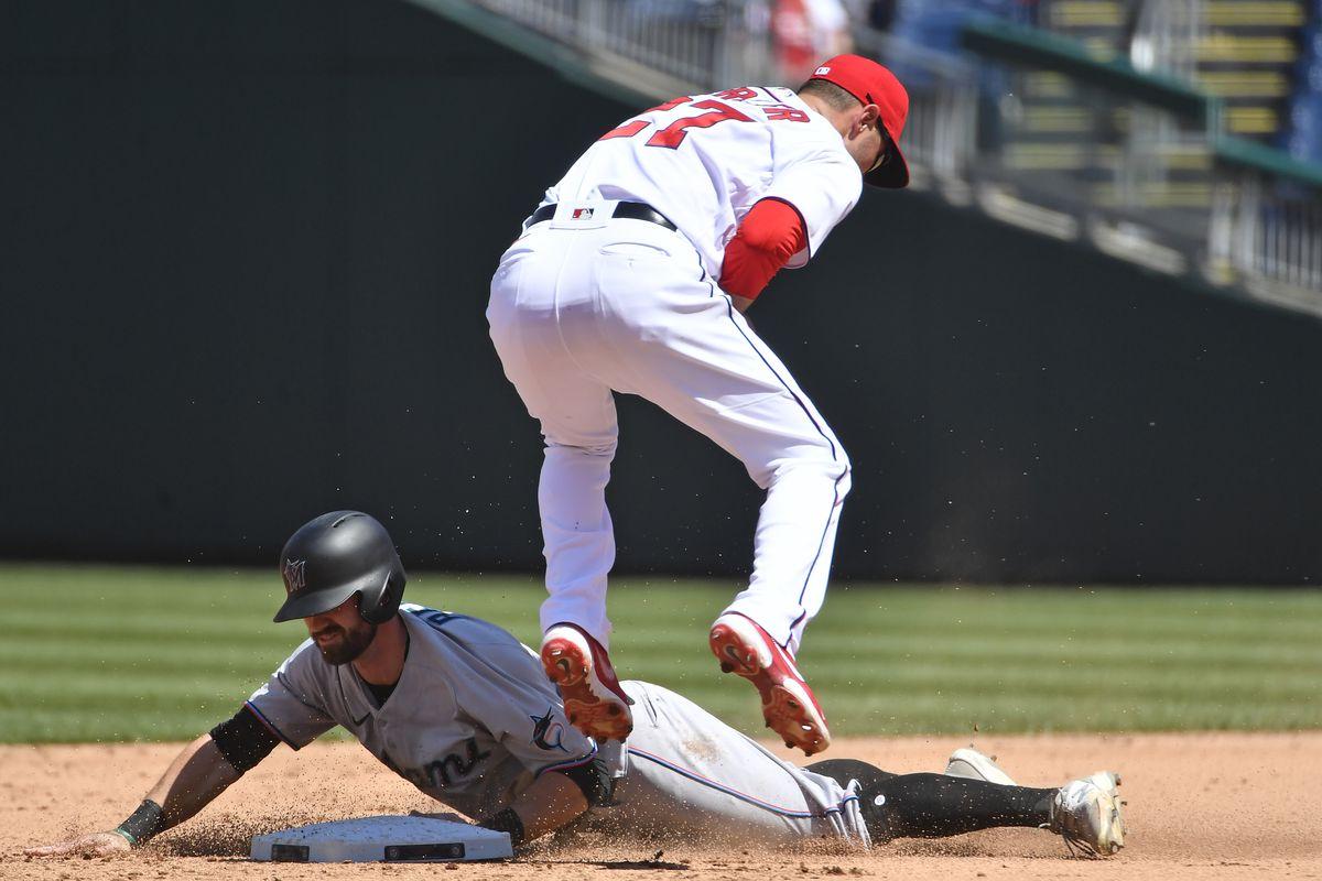 Miami Marlins third baseman Jon Berti (5) steals second base under the tag by Washington Nationals second baseman Jordy Mercer (27) at Nationals Park.