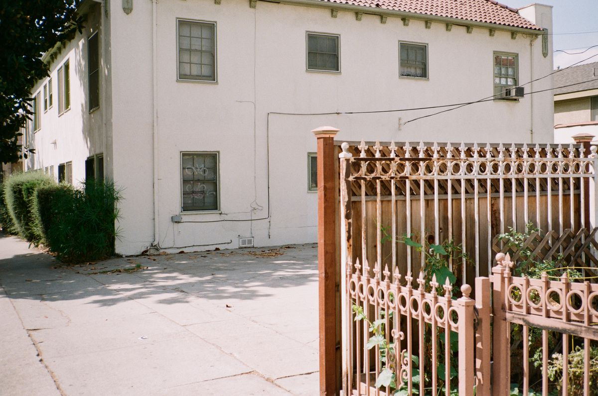 In the foreground, a faded metal fence with vines growing inside of it, in front of an open lot, next to an off white, two story, building with bushes in front and roof tile.