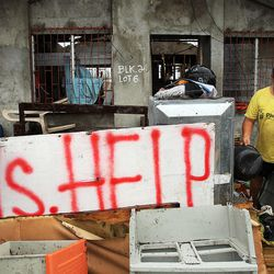 Edwin Dapon clears rubble from his home in Tacloban, Friday, Nov. 22, 2013.