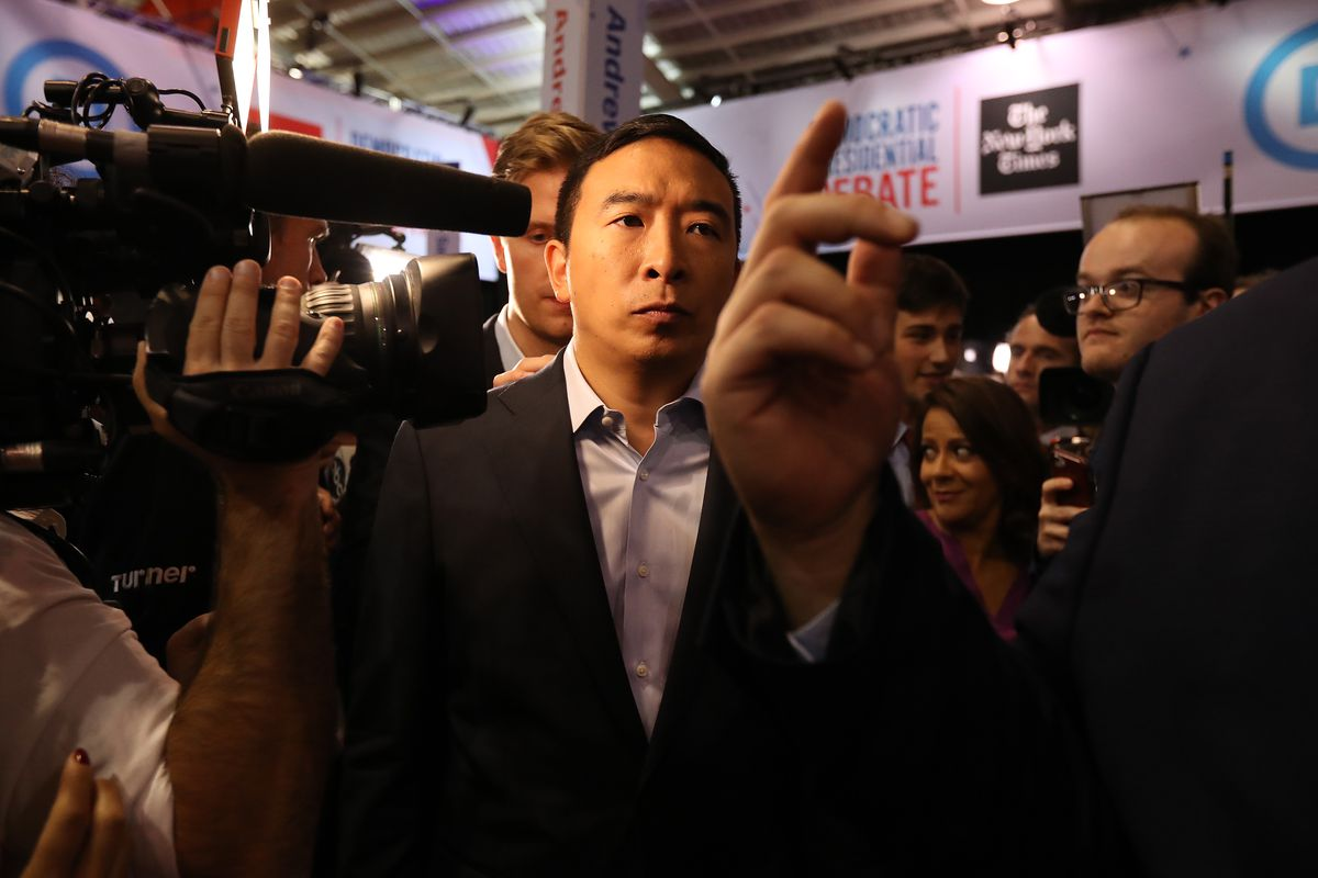 Presidential candidate Andrew Yang walking around a debate hall surrounded by reporters.