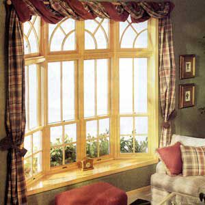 THIS 30-DEGREE unit from Eagle Windows & Doors is made of reverse-cottage double-hung windows. Fixed-light transoms with semicircular grilles sit above the window.