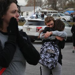 A mother waits for her child as Dallas Tucker holds his girlfriend, Alyssa Miller, a sophomore, after a lockdown at the high school was lifted Thursday, Dec. 3, 2015. Pleasant Grove High School was placed on lockdown after receiving reports of a man with a weapon inside the school.
