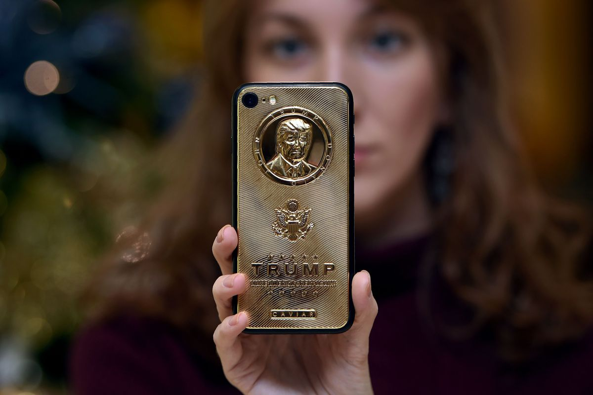 An employee of Caviar Phones displays a special gold-plated iPhone 7 smartphone bearing the likeness of then-U.S. President-elect Donald Trump in the company's boutique outside Moscow on Nov. 14, 2016.