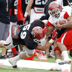 Utah walk on #59 Sam Nielson, left, works to bring down teammate #35 Richie Vakapuna during a drill as Utah practices at Rice Eccles Stadium Tuesday, April 10, 2012.