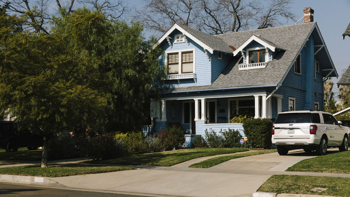 A blue house with white trim and a gray roof is partially concealed behind a large tree. The home has a covered front porch.