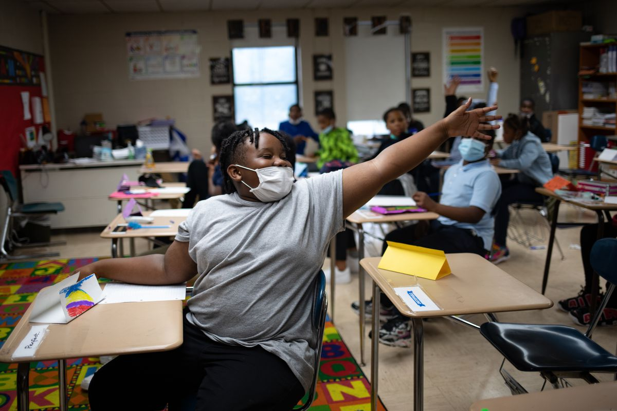 A student emphatically raises their hand during an exercise in class. The student and their peers are all wearing protective masks at their desks in the classroom.