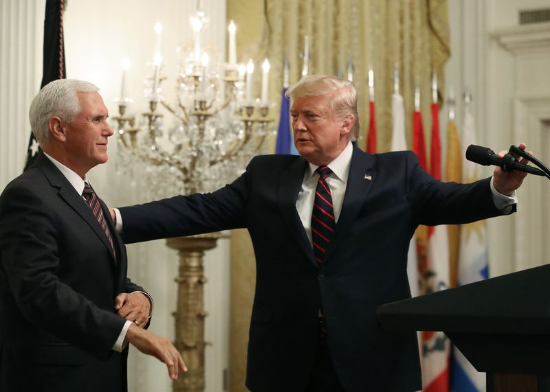 President Donald Trump yields the podium to Vice President Mike Pence at an event in The East Room at the White House.