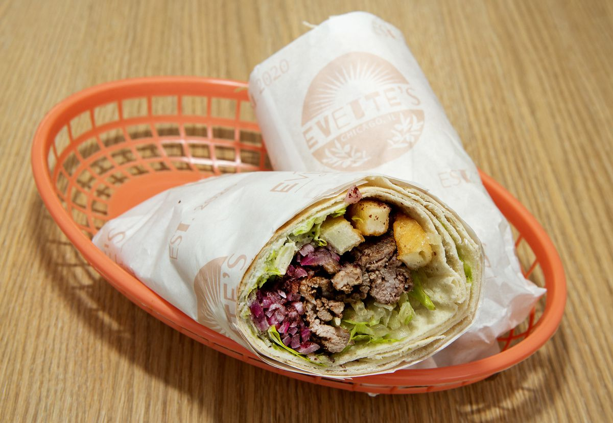 A rolled up wrap wrapped in paper with meat and veggies stuffed inside.