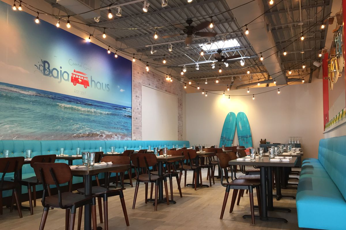A dining room with an ocean mural, two surfboards in the back and a ceiling with strings of lights