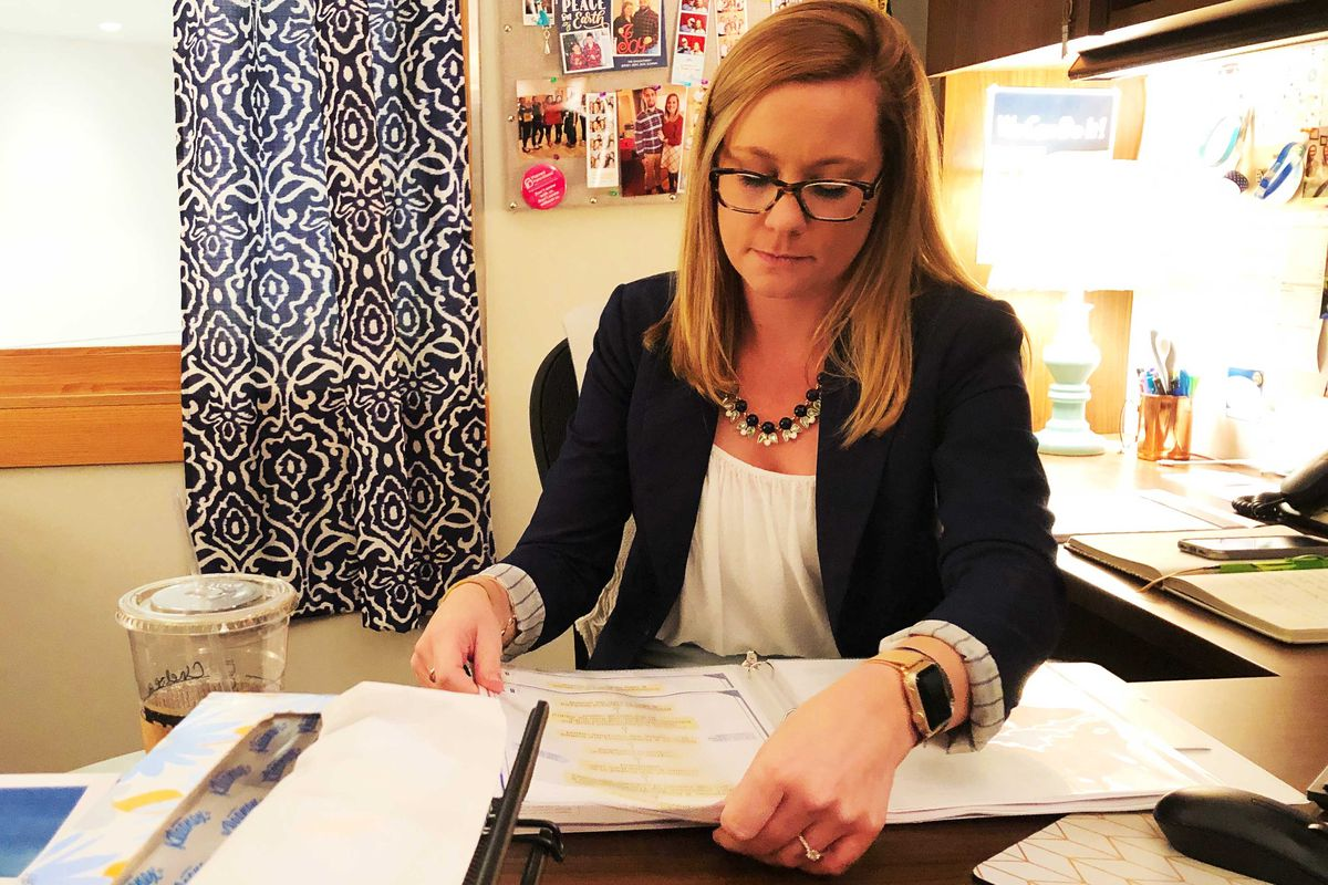 Chelsea Jacoby seated at her desk in her office, flipping through a binder.
