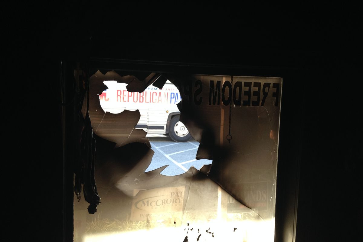 """The window of the Orange County (NC) Republican Party headquarters, damaged by a bottle containing a """"flammable liquid"""" overnight Sunday."""