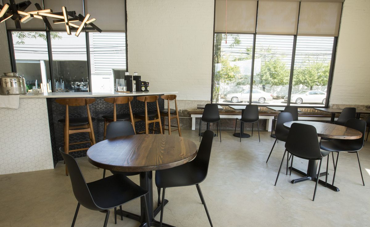 A modern-style cafe with round tables, a coffee counter, two windows, and modern light fixtures.