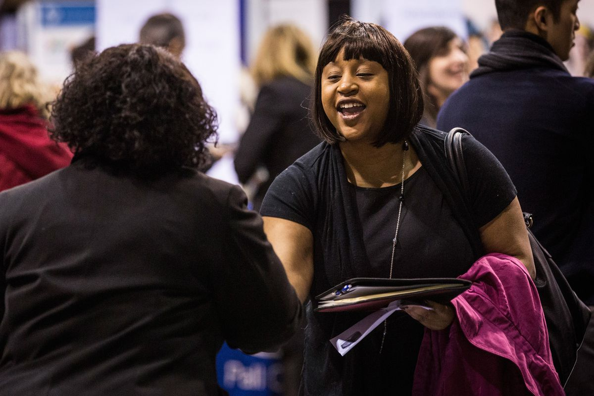A woman greets a potential employer at a New York City job fair for veterans.