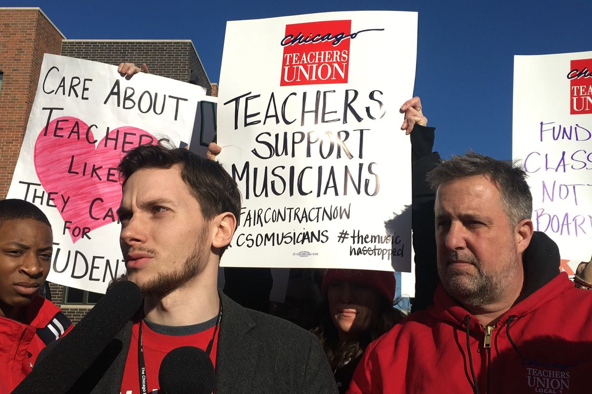Teacher Andrew Van Herik, center, with microphone, and Chicago Teachers Union charter division President Chris Baehrend speak at a press conference outside the Chicago High School of the Arts.