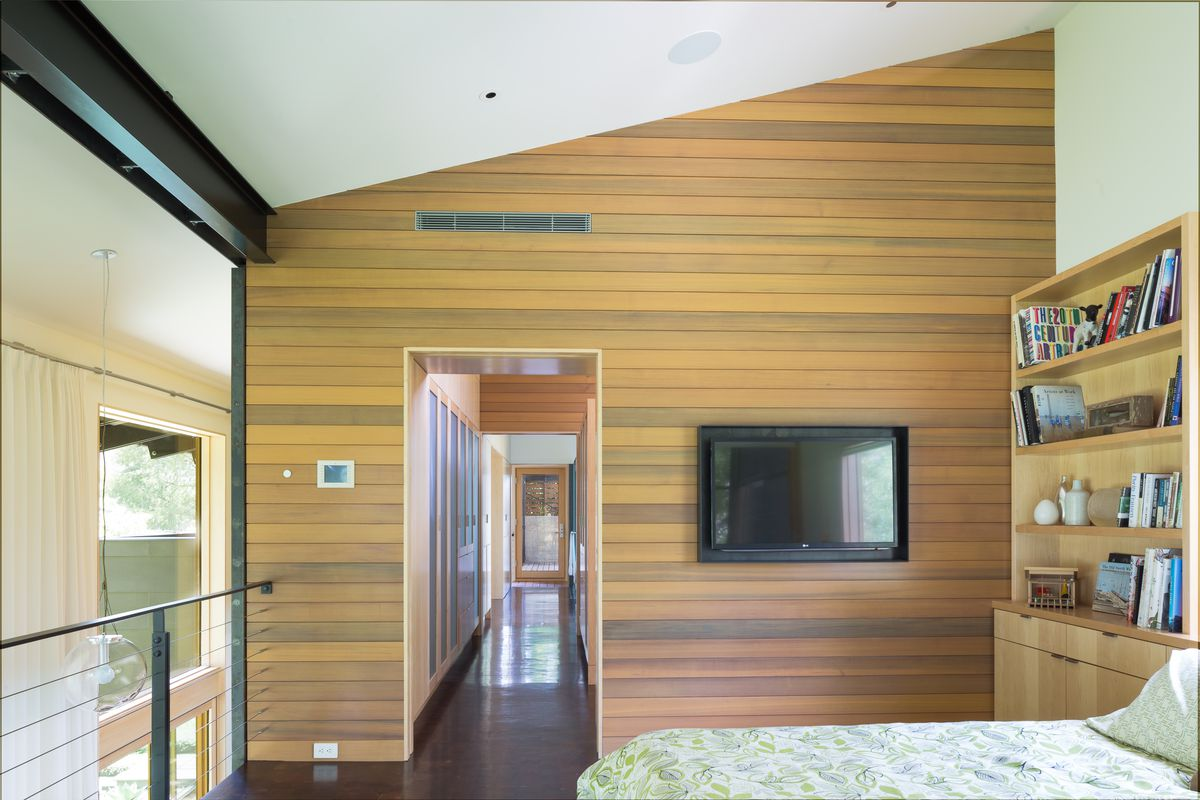 bedroom with wooden wall, railing, open to two-story living room, long hallway