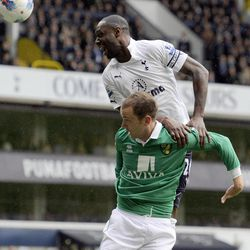 Tottenham Hotspur's Ledley King, top, tries to stop  the shot from Norwich City's Aaron Wilbraham during their English Premier League soccer match at White Hart Lane stadium, London, Monday, April 9, 2012.