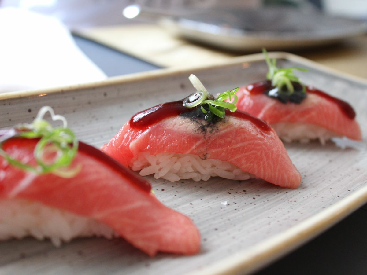 Three nigiri tuna rolls on a white plate with soy sauce on top