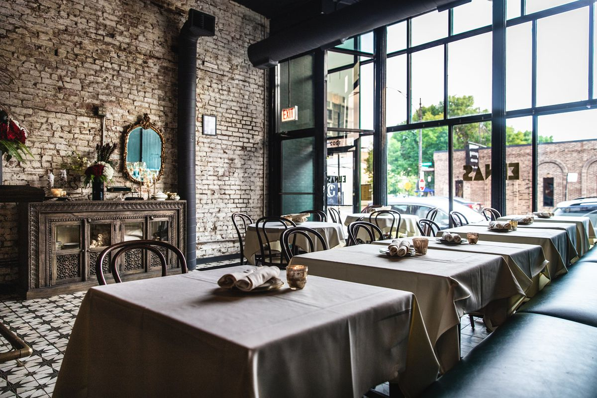 A dining room with exposed brick wall, antique mirror and credenza on the left, tables with white tablecloths and a blue banquette on the right.