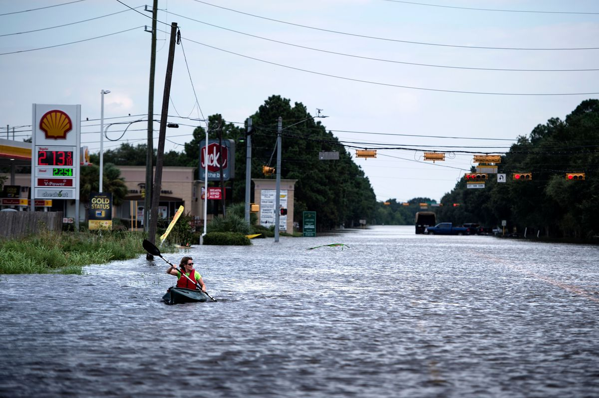 A woman in a kayak paddles down a flooded street.