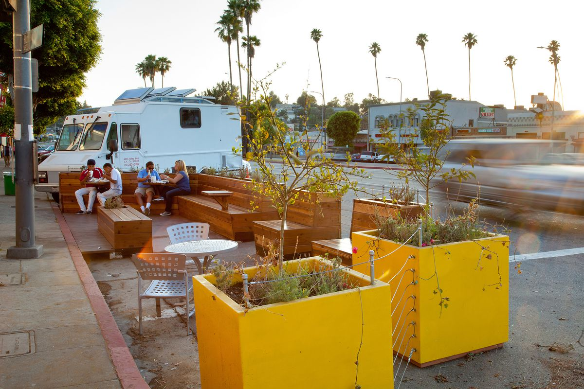 A wooden parklet with planters near a food truck in Los Angeles.
