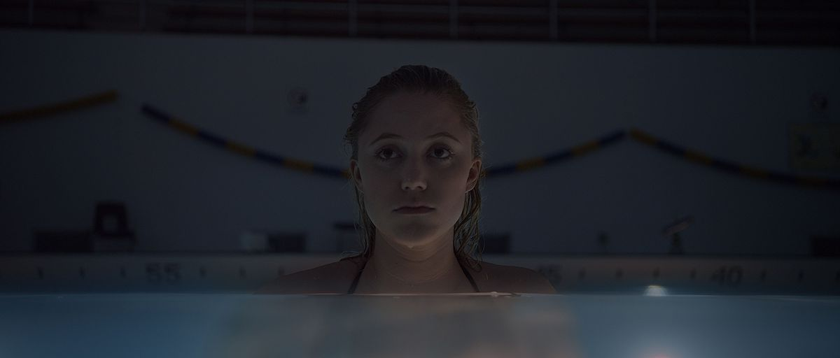A woman waits in a swimming pool in It Follows