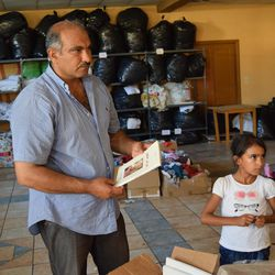 Farez Al-Hamdan, 47, and his daughter Cidra, 8, help organize donations at the Kyllini refugee camp in Myrsini, Greece, July 11, 2016. The camp was previously a luxury resort before it fell into disrepair and was later turned into a refugee camp.