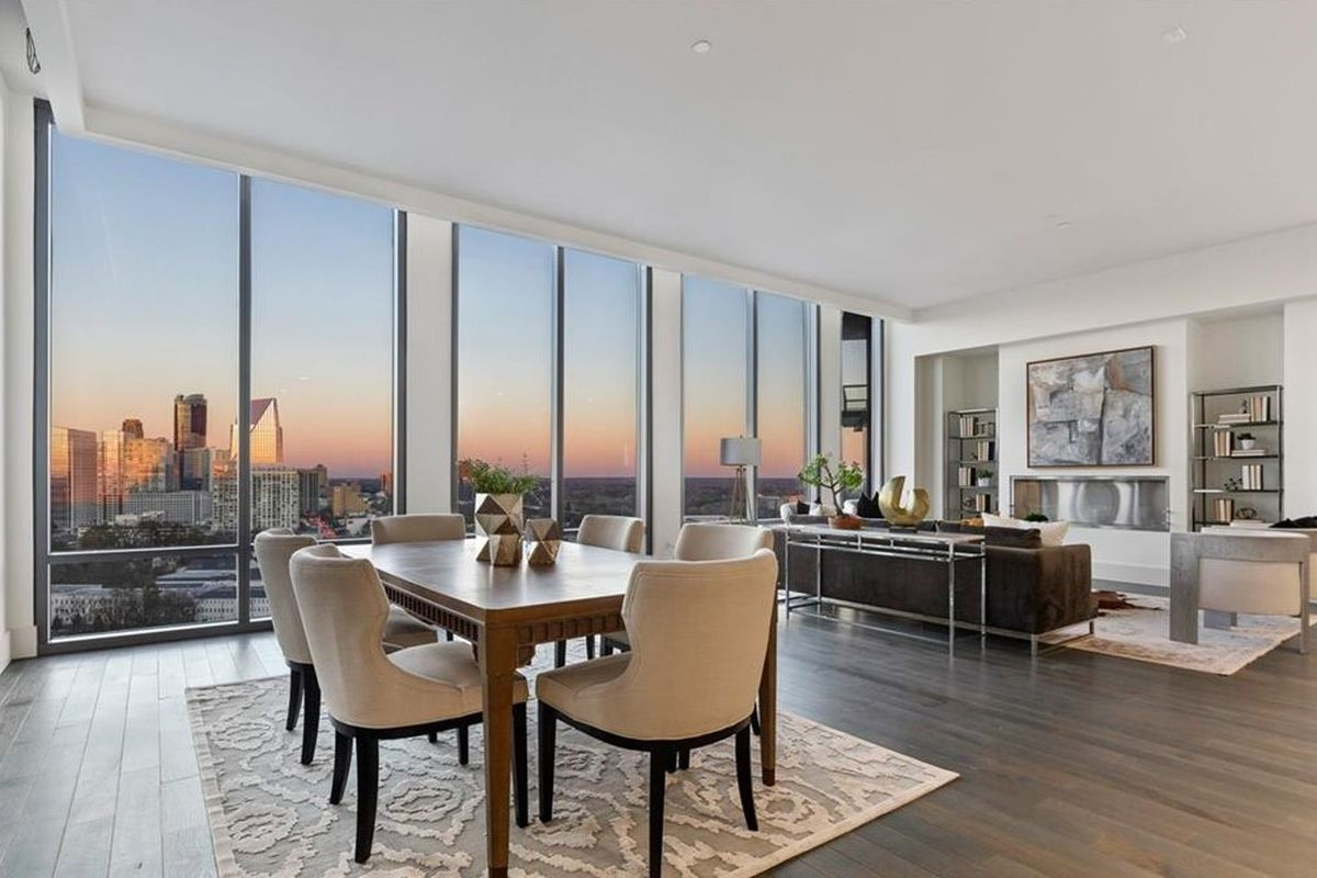 A condo living and dining room with white walls and a city in the evening beyond the huge windows.