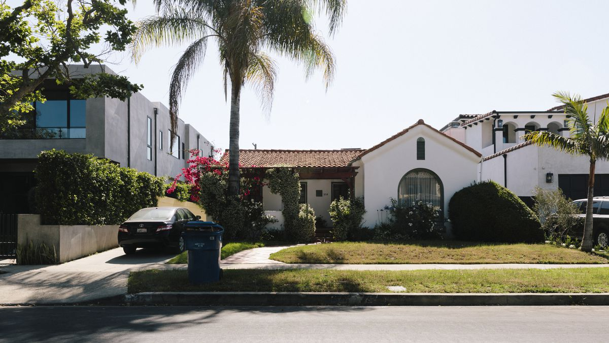 A large white house with a lawn in front of it. There is a driveway with a car. There are palm trees in front of the house.