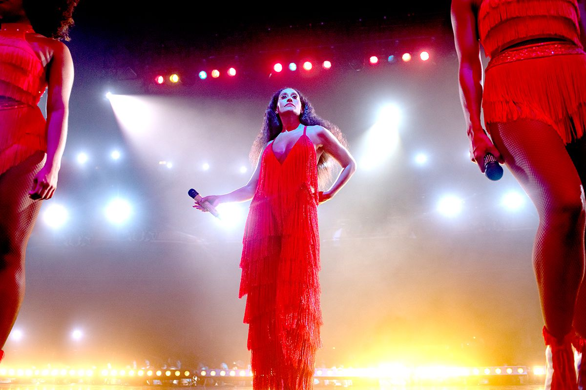 A woman in a red dress stands on a stage, performing.