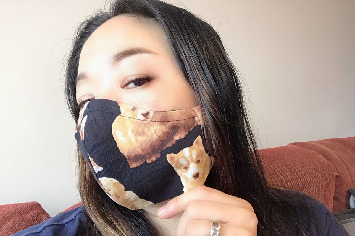 Former Seattle cook Atina Tan wears a cloth mask with corgis on it.