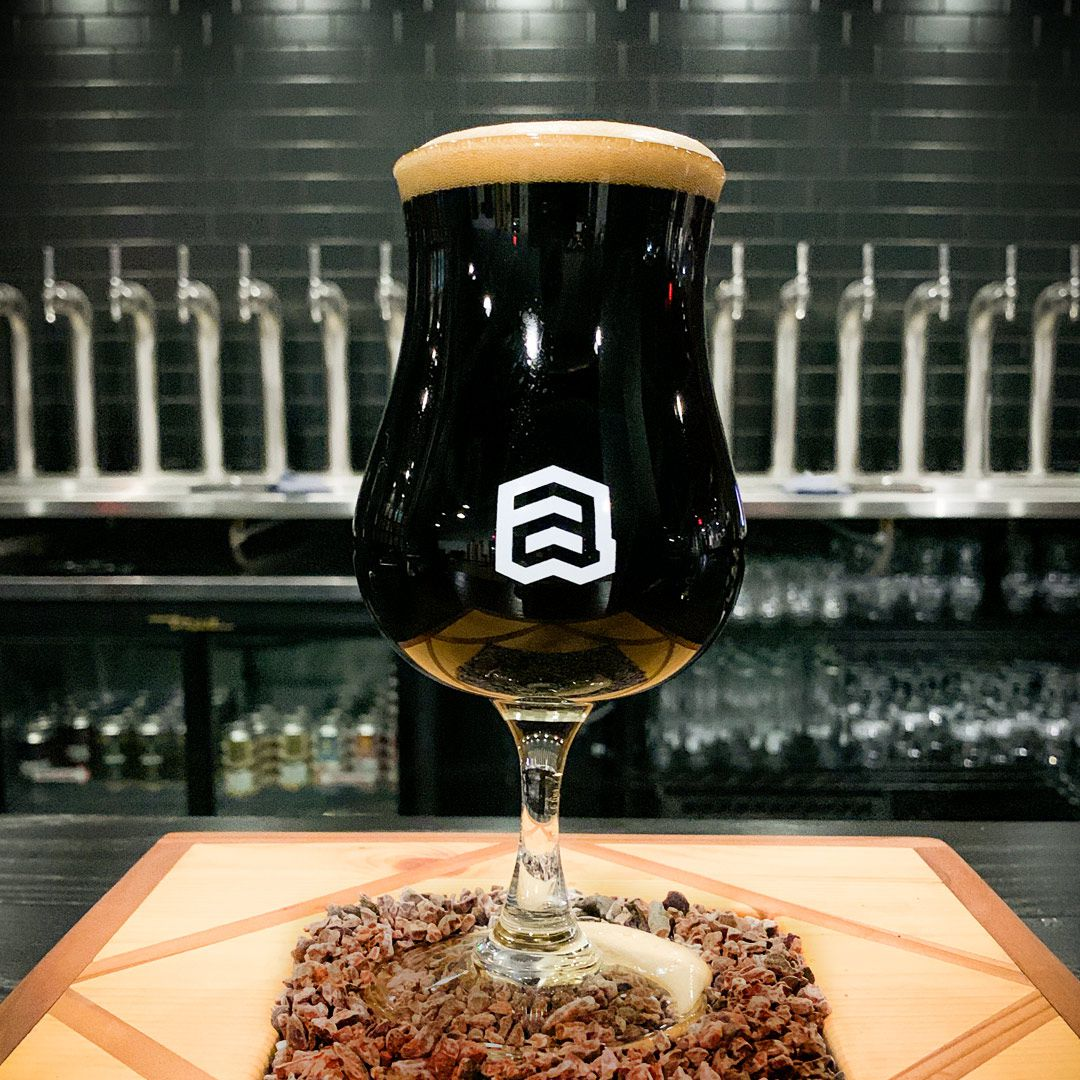 A bell-shaped glass filled with dark brown beer