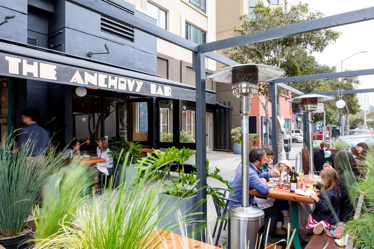 Outdoor seating at Anchovy Bar on a sidewalk. Some diners are seated under an overhang. A family with children sits in the foreground. Plants and heat lamps are scattered about.
