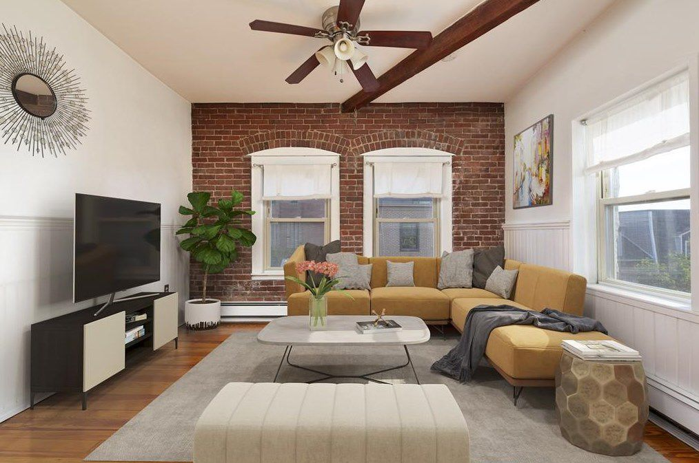 A living room with a L-shaped couch at one end, facing a mounted TV, and there's a ceiling fan.