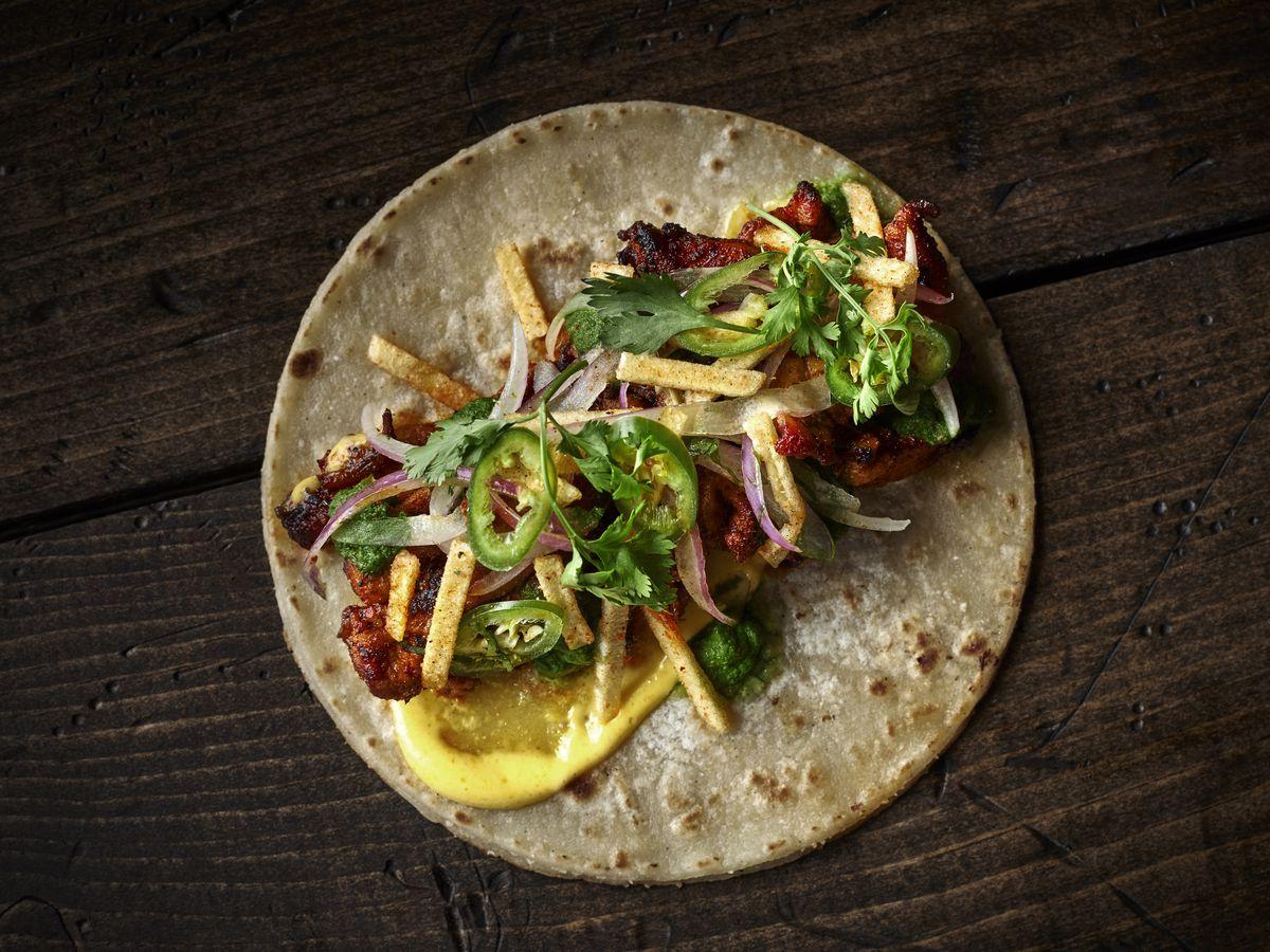 """Taco Bamba's El Rico Pollo taco with green chile puree, aji amarillo aioli, salsa criolla, and crispy potato to """"Peruvian-ish"""" chicken."""