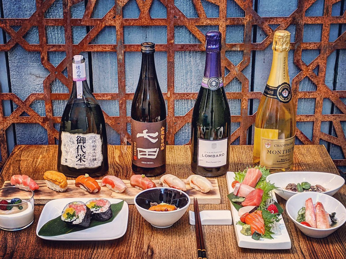 A table with bottles of wine in the background and plates of sushi in front.