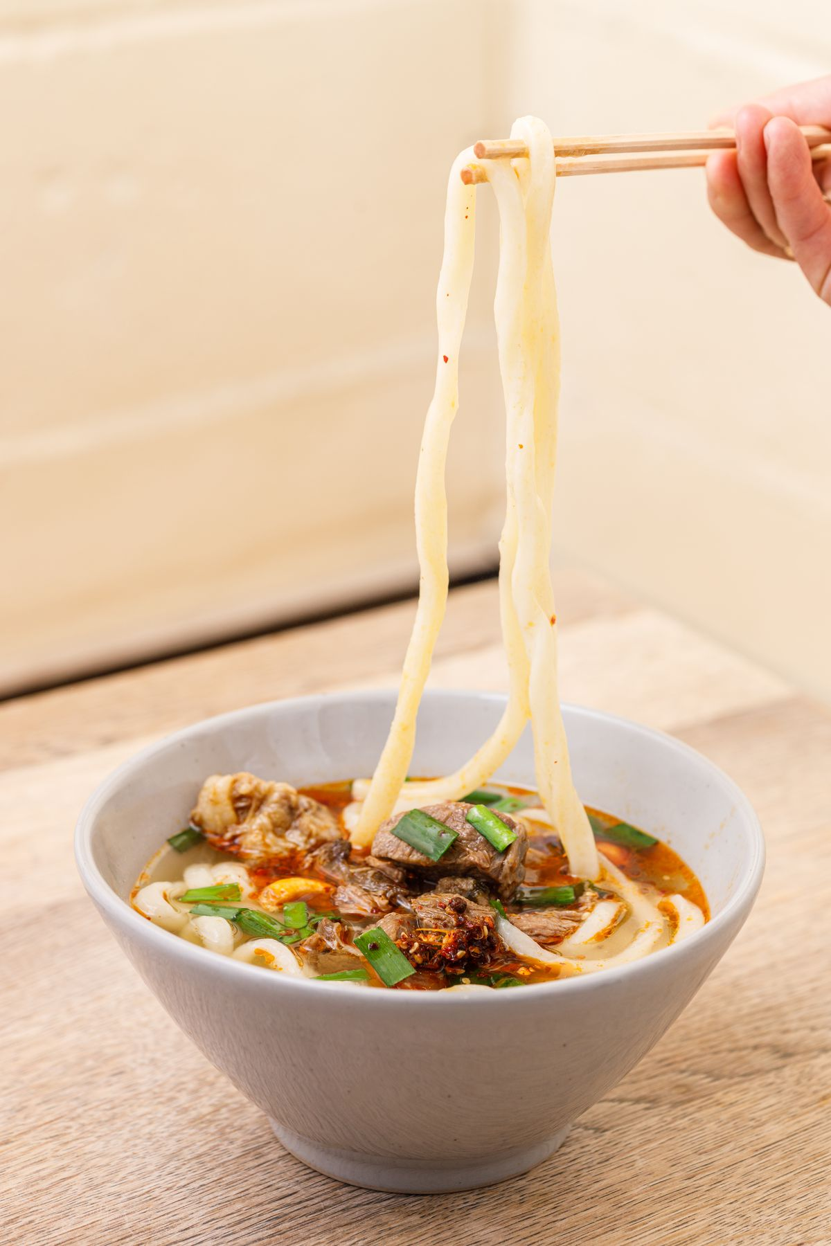 """The playfully named Ko Meaty! — a slow-braised beef shin broth with chilli oil cossets the udon, which are being """"noodle-pulled"""" out of the bowl, in a new dish for this restaurant only."""