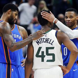 Utah Jazz guard Donovan Mitchell is greeted by Oklahoma City Thunder guard Russell Westbrook, right, forward Paul George, left,  and forward Carmelo Anthony following NBA basketball in Salt Lake City on Saturday, Dec. 23, 2017.