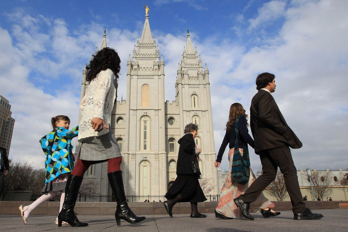 People walk pass the Salt Lake Temple on the way to the Conference Center during the opening session of the two-day general conference of The Church of Jesus Christ of Latter-day Saints on Saturday, April 5, 2014, in Salt Lake City.