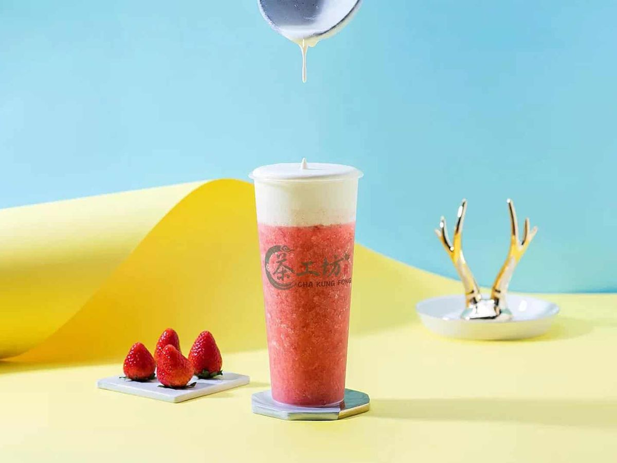 Glamour shot of a skinny plastic cup of a frozen fruit tea with a foamy cap. It's pictured on a pale yellow surface on a blue background with fresh strawberries to the side.