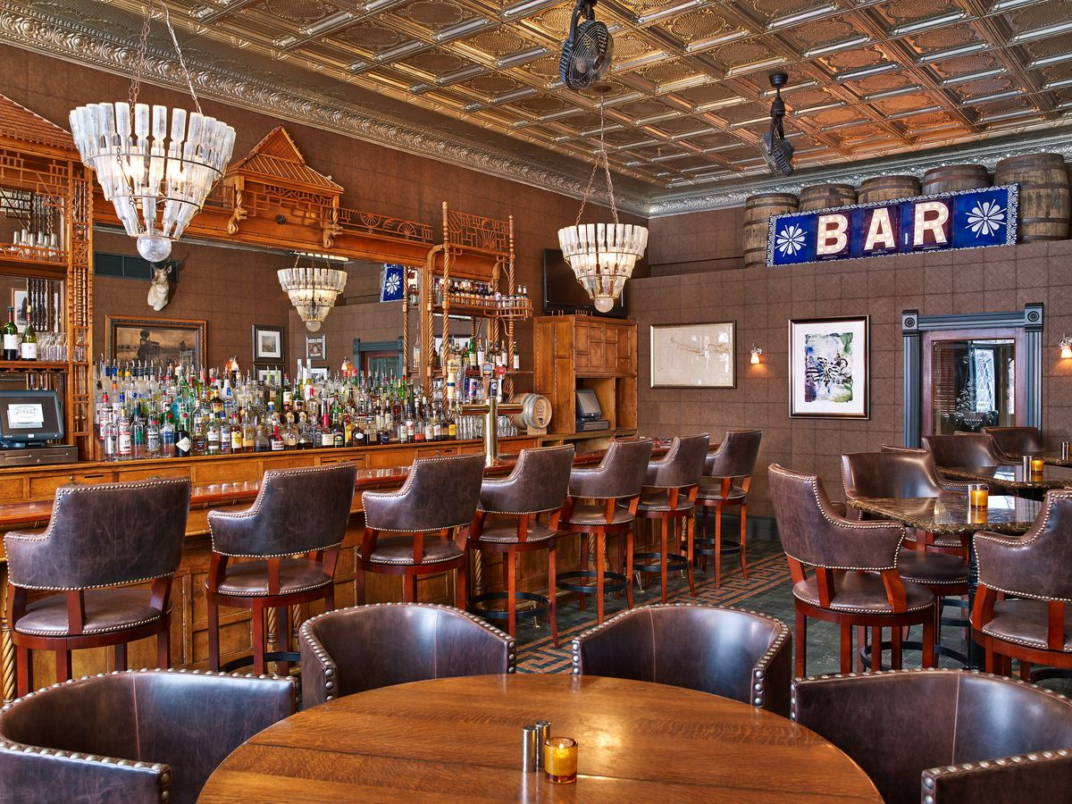 A bar interior, with high wood tables and a bar with leather stools, ornate chandeliers over the bar, and large carved wood mirror on the backbar