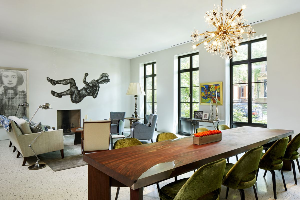 A large wooden table has a metal inset. A fireplace is without a mantel or ornamentation.