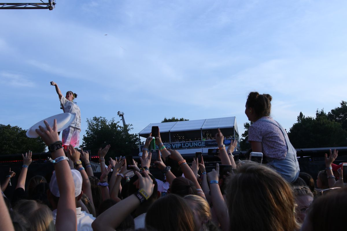 A young girl in the crowd on her mother's shoulders stares at Billie Eilish during the show.