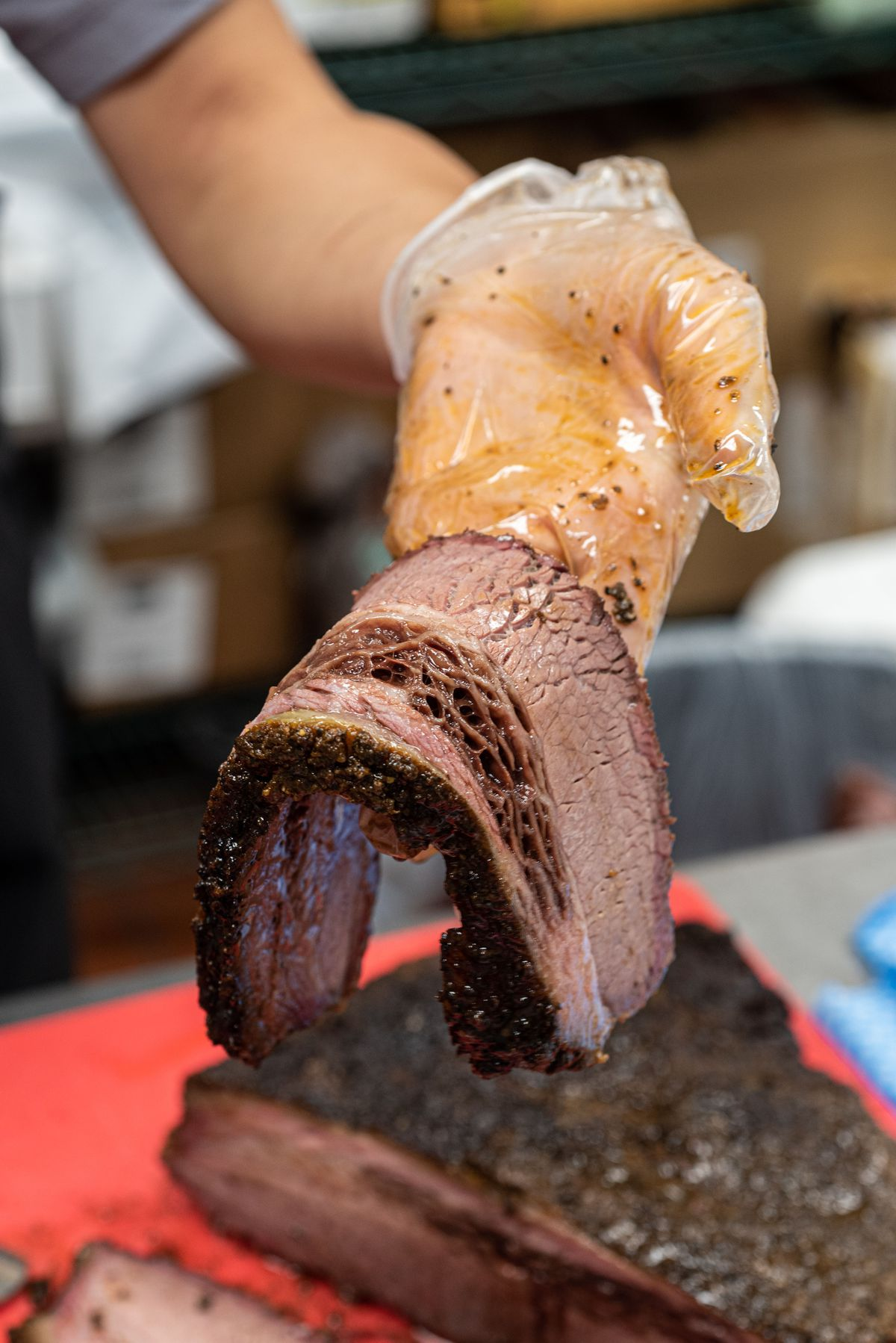 A thick slice of brisket bending over a gloved hand.