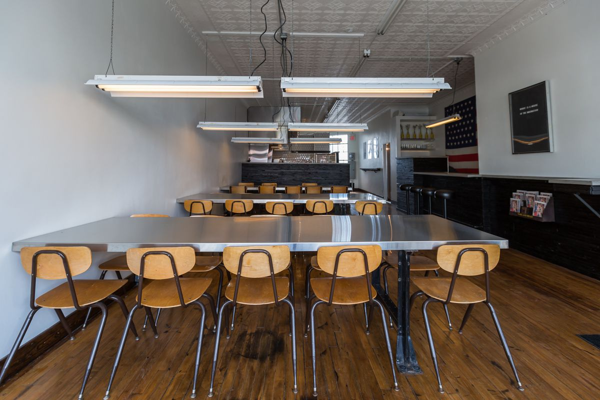 Tables in rows with school house-style wood chairs at Gather in Eastern Market.
