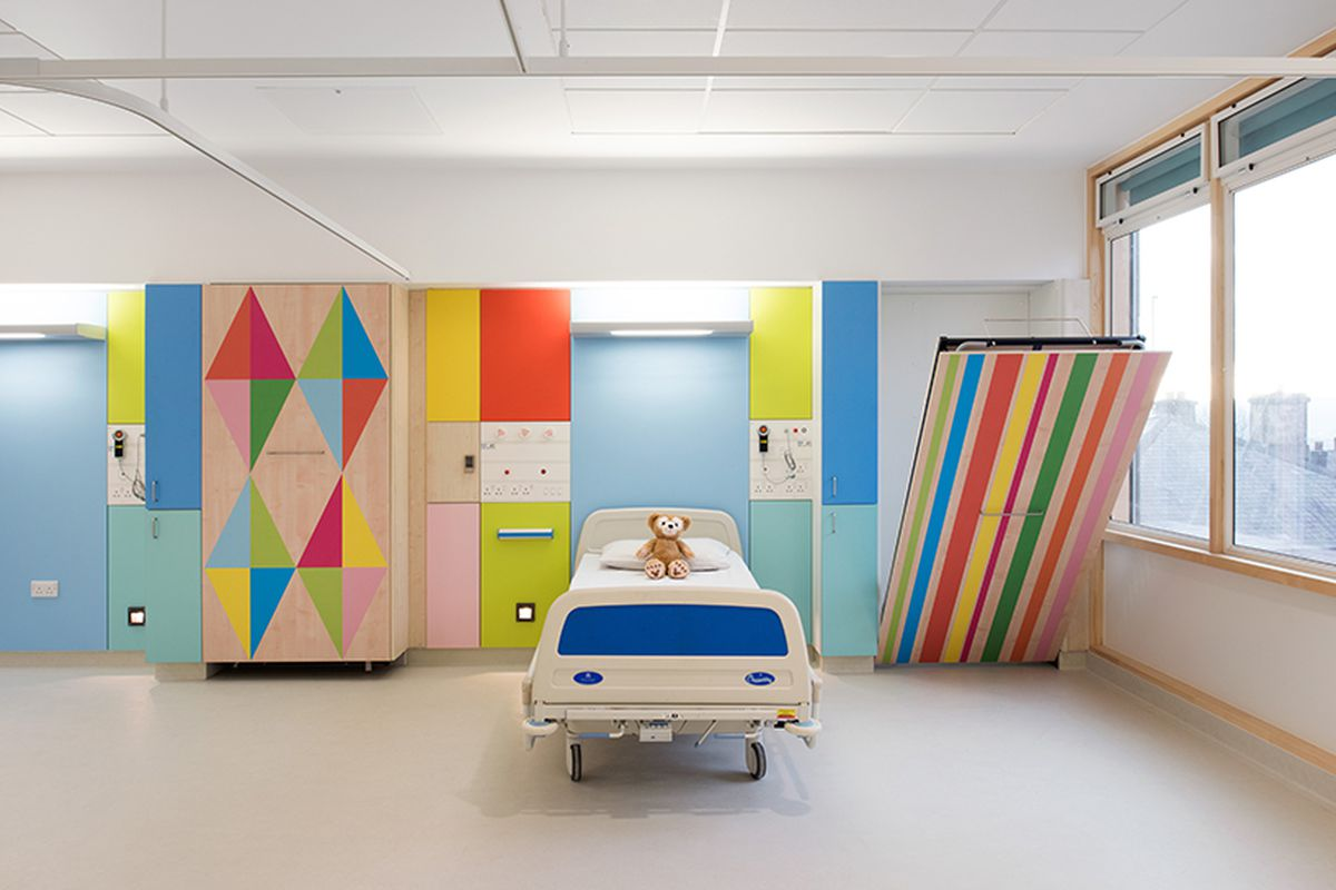 Interior of a white hospital room with panels of bright colors and patterns behind the bed with a teddy bear on top of it. There's also a murphy bed pulled partly down whose bottom is striped with rainbow colors.