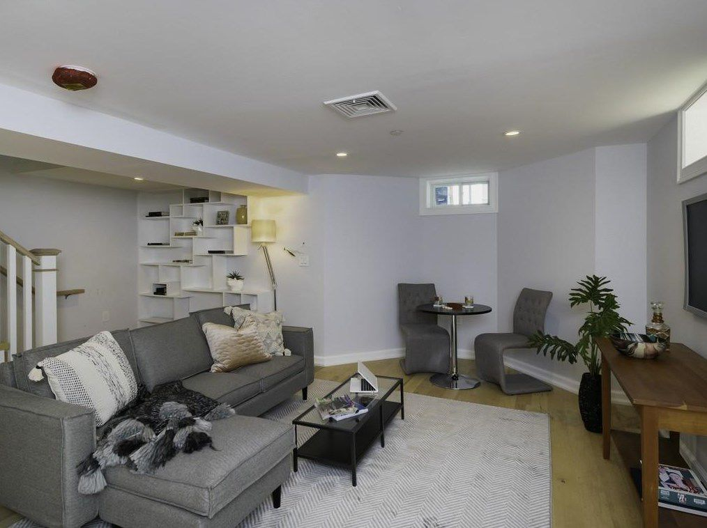 A basement with a couch and then two chairs around a small table.