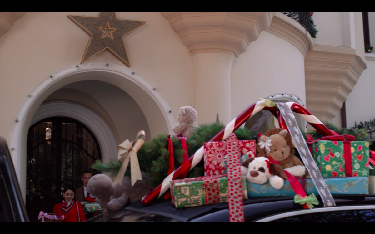 A black car with presents and stuffed animals strapped to the roof