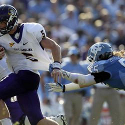 North Carolina's Tommy Heffernan (55) reaches for East Carolina quarterback Shane Carden (5) during the first half of an NCAA college football game in Chapel Hill, N.C., Saturday, Sept. 22, 2012.