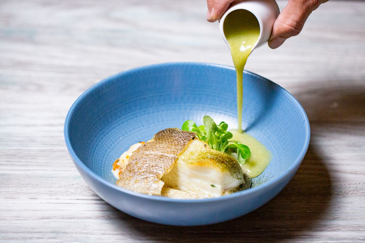 A server pours salsify puree into a plate of seared Icelandic cod with green apple, celery, and seaweed dust
